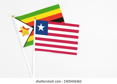 Liberia and Zimbabwe stick flags on white background. High quality fabric, miniature national flag. Peaceful global concept.White floor for copy space.