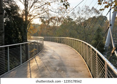 Liberty Bridge - pedestrian suspension bridge curving into the sunlight as it spans the Reedy river in downtown Greenville, South Carolina