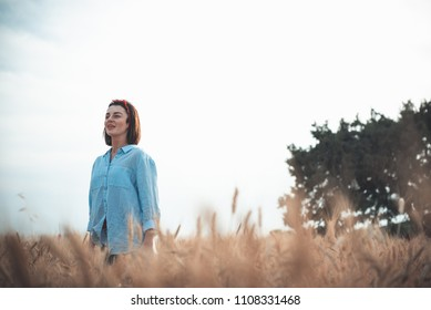 Liberty peace of mind concept. Attractive young woman is walking in golden wheat field with tree in background. She is looking forward with slight smile. Copy space in the right side
