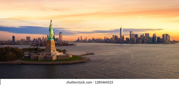 Liberty statue in New York city with manhatttan background and sunset, New York, USA