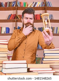 Librarian concept. Man on thoughtful face stands between piles of books, while holds hourglass, bookshelves on background. Teacher, scientist with beard stands at table with books, defocused.