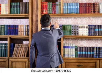 Librarian stands near bookcase. Work, historical research, profession, intelligence, choice concept. Books and education. Man in formal suit stands in library. Man choose book in vintage interior.