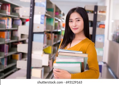 Librarian Woman in the foreground is Holding a books. Young Asian Woman are reading in the modern library. People with Education concept.
