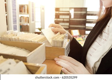 Librarian woman using old paper card catalog to find some information. Close up view