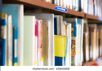 Library with book shelves full of book arranged in order on regals. Close up full frame view