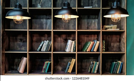 library. Bookshelves with books and three burning lamps. Few books. Concept: librarytek, education, reading