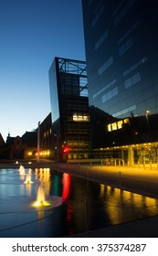 "Library building known as the ""Black Diamond"" on the harbor front in Copenhagen at night. Scenic view of Scandinavia architecture. Deep dark scene near flat fountain, nordic landmarks, Denmark."