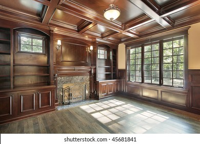 Library in luxury new construction home with fireplace