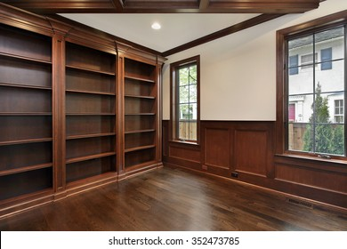 Library in new construction home with wood ceiling beam