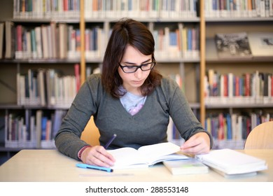 in the library - portrait of pretty female girl studying for exam