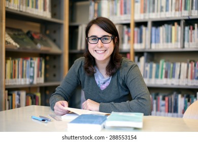 in the library - portrait of pretty female student with books while works and smiles