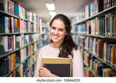 In the library - pretty female student with books working in a high school library.
