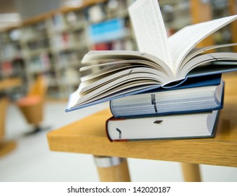 library with stack of books opened.