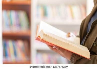In the library - Teenage girl student with books reading in a high school library.