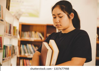 In the library - Young girl student with books working in a high school library.