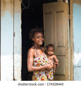 LIBREVILLE, GABON - MAR 6, 2013: Unidentified Gabonese woman holds her baby and stays at the porch in Gabon, Mar 6, 2013. People of Gabon suffer of poverty due to the unstable economical situation