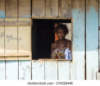 LIBREVILLE, GABON - MAR 6, 2013: Unidentified Gabonese woman looks trough the open window in Gabon, Mar 6, 2013. People of Gabon suffer of poverty due to the unstable economical situation