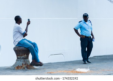 LIBREVILLE, GABON - MAR 6, 2013: Unidentified Gabonese man takes pictures of a locan police man in Gabon, Mar 6, 2013. People of Gabon suffer of poverty due to the unstable economical situation
