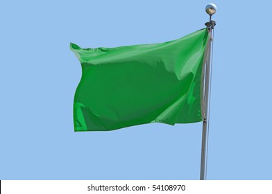 Libyan flag flying in a stiff breeze against a clear blue sky.