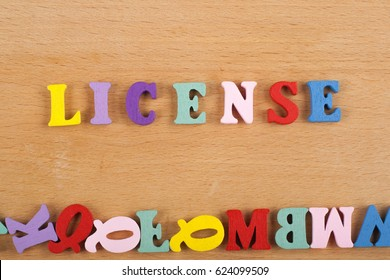 LICENSE word on wooden background composed from colorful abc alphabet block wooden letters, copy space for ad text. Learning english concept