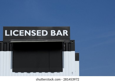 licensed bar sign on a black and white building with blue sky copy-space