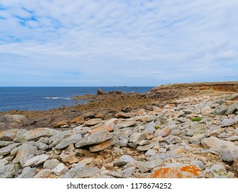 Lichen covered boulders of varying sizes cover the shore to the Celtic Sea in Brittany