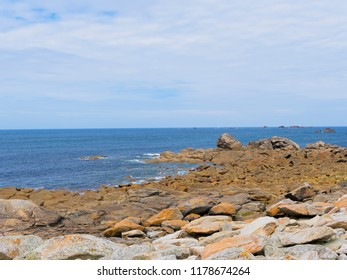 Lichen covered rocks of varying sizes cover the shore to the Celtic Sea in Brittany