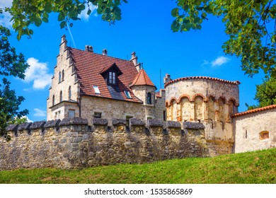 Lichtenstein Castle in summer, Baden-Wurttemberg, Germany. It is a landmark of Germany. Scenic view of famous Lichtenstein Castle and fortress wall. German castle in Swabian Alps with foliage frame.