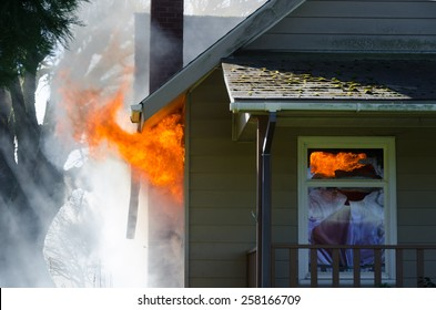 Licks of flame burst out of the window of a house surrounded by thick black smoke