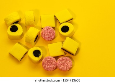 Licorice Allsorts againts a yellow background. This candy is typical British.