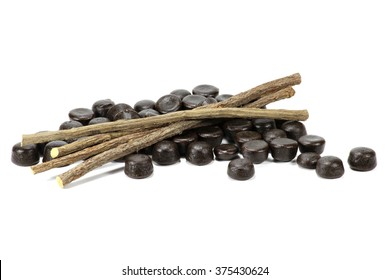 licorice candies with dried sticks of liquorice root isolated on white background