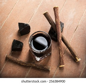 Licorice liqueur with pure blocks and roots on wooden table.