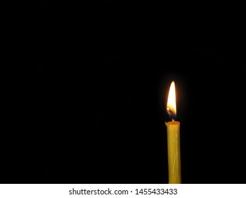 Lid yellow candle on the black background. Candle light and flame background. Hope and religion concept.
