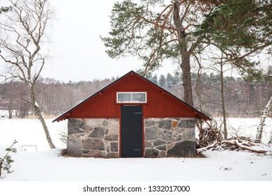 LIDINGOE, STOCKHOLM, SWEDEN, FEBRUARY 2018, a small stone and wooden outhouse by a frozen lake on a cold and grey day.