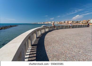 Lido di Ostia, ITALY - September  14, 2016: Relaxing people on the pier (Pontile Di Ostia) near beautiful beach Lido di Ostia ( Lido di Roma), Italy.