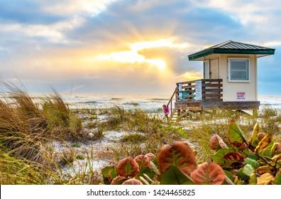 Lido Key Beach Lifeguard Tower at Sunset in Sarasota, FL. A family enjoying the sunset at the beach.