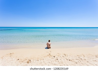 Lido Venere, Apulia, Italy - A young mother sitting on the beach looking towards the horizon