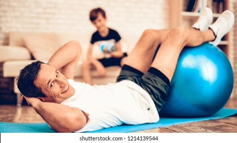 Lie on Floor with Fitball. Sport at Home. Gym Mat. Doing Sports. Man and Boy Train at Home. Health Concept. Healthy Lifestyle. Swiing Press on Floor. Man and Boy with Fitball. Swing Press on Fitball.