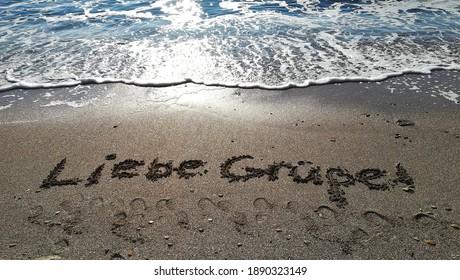 Liebe Grüße vom Meer; Many greetings from the seaside. Written on the sand. - Shutterstock ID 1890323149