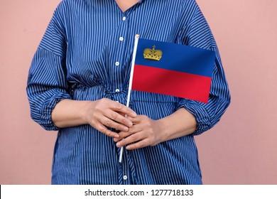 Liechtenstein flag. Close up picture of woman's hands holding a national flag of Liechtenstein.
