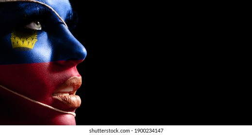 Liechtenstein flag painted on a face of a young woman, national flag on face