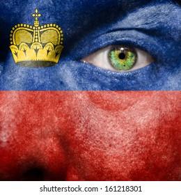 Liechtenstein flag painted on a man's face with green eye to show Liechtenstein support