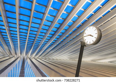 LIEGE, BELGIUM - DECEMBER 12, 2014: Beautiful abstract view of the interior of the modern architecture railway station Liege-Guillemins with a clock in the blue hour in Belgium on December 12, 2014