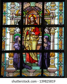 LIER, BELGIUM - MAY 25: Stained glass window depicting Jesus and two catholic nuns in the Church of the Beguinage in Lier, Belgium, on May 25, 2013.