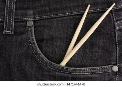 Сhopstick lies in black jeans pocket.
