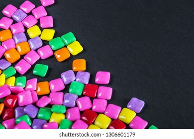lies a lot of rainbow colored chewing gum on a black background
