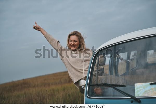 Das Leben ist toll! Attraktive junge Lächlerin, die sich aus dem Fenster des Van auslehnt und während der Autofahrt gesinnt ist