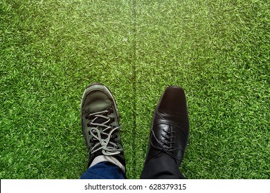 Life Balance concept for Work and Travel present in top view position over green grass field by half of business oxford and adventure shoes