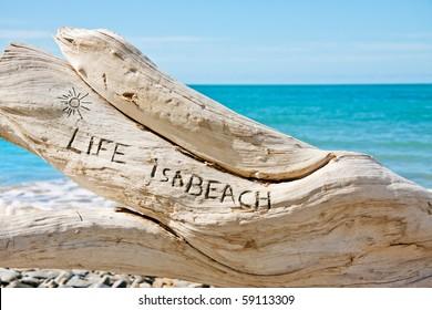 'Life is a beach' written on a log on a beautiful tropical beach