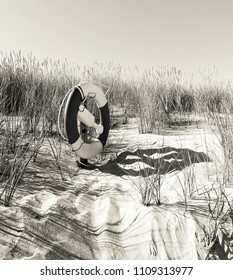 Life bouy on sand dune in sunshine at the beach for safety, textured in soft black and white tones for an aged look.